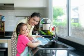 Beautiful Asian Mother And Daughter Having Fun While Washing Dishes Together With Detergent On Sink  poster