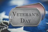 Worn US American dog tags on USA flag with Veterans Day engraved text poster