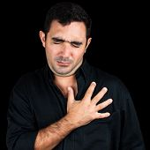 Young man feeling pain on his chest and touching it with his hands isolated on black