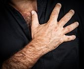 Close up of a hand grabbing a chest on a black background, useful to represent a heart attack or any