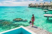 Luxury overwater bungalows Tahiti resort woman going snorkeling from private hotel room on Bora Bora poster