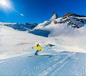 Woman skiing on fresh powder snow with Matterhorn in background, Zermatt in Swiss Alps. poster