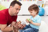 Father and toddler son playing on the floor with finger puppets