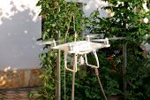 Modern White Quad Copter Drone With 4k Digital Camera Is Flying In The Air, To Take Photos And Recor poster