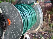 Green Gardening Hose For Watering Flowers And Grass Wrapped Around The Aluminum Carrier. Garden Wate poster
