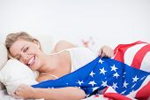 Laughing blonde woman with a US flag in her bed