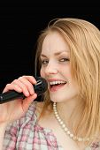 Fair-haired woman singing against black background