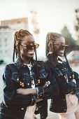 A Cheerful Smiling Happy Young Black Female With Braids And In A Denim Jacket And Sunglasses Is Lean poster