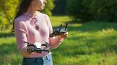 A Young Woman In A Clearing In A Park Launches, Checks, Holds A Drone, In One Hand, In The Other Con poster