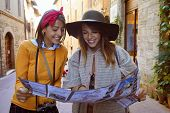 Cheerful smiling  women on vacation sightseeing city with map poster