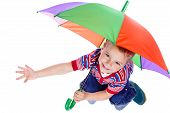 Little boy sitting under umbrella
