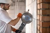 The Industrial Builder Works With A Professional Angle Grinder To Cut Bricks And Build Interior Wall poster