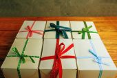 Stack Of Gift Wrapped Christmas Presents. A Stack Of Gifts Of White Colors Tied With Different Ribbo poster