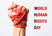Red Rope On Fist Hand With World Human Rights Day Text On White Background, Human Rights Day Concept poster