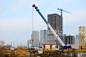 Installation Of A Tower Crane. A Truck Crane Lifts A Load At A Construction Site.installation Of A T poster