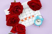 Blue Alarm Clock And Red Rose Flowers On Menstrual Period Calendar With Red Cross Marks poster