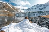 Young girl relaxing in comfy bed in wild nature with a view on beautiful landscape in cold season. D poster