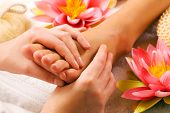 stock photo of reflexology  - Woman enjoying a feet massage in a spa setting  - JPG