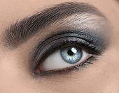 Beautiful woman eye close-up. Young Woman Blue one eye macro shoot. Holiday smoky eyes make-up, Macr poster