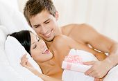Man lying in bed gives present wrapped with pink paper to girl
