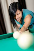 Woman playing billiards. Spending free time on gambling
