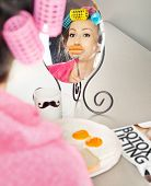 Woman with sausages on a fork simulating lip enhancement while having breakfast