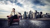 young businessman sitting on the armchair with cityscape behind