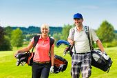 foto of golf bag  - Young sportive couple playing golf on a golf course - JPG