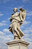 Statue of an Angel carrying a symbol of the Passion on Sant Angelo bridge Rome Italy. Angel created by renaissance artist, Bernini, against blue sky