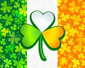 stock photo of triskele  - Irish flag background made from green and orange clovers with big clover on it - JPG