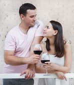 Couple Enjoying A Glasses Of Red Wine