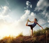 Young slim lady doing stretching exercises on a rural path with grass and cloudy sky on the backgrou