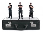 Three security guys standing on black cipher suitcase shot on white, security concept