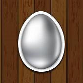 Shiny sliver Easter egg on wooden background.