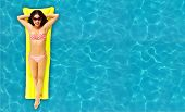 Beautiful Woman relaxing in a pool. Summer vacation.