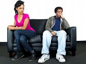 stock photo of cheater  - young black male and female couple isolated on a couch - JPG
