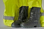 stock photo of hse  - mid calf length black safety in front of high vis coat on white background - JPG