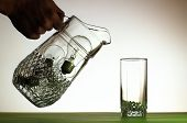 Hand Pouring From Jug Of Light Bulbs Into Glass