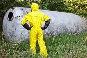 image of toxic substance  - technician in uniform examining large stainless tank - JPG