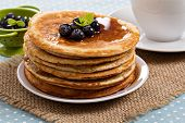 Stacked pancakes with berries and maple syrup