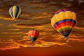 Colorful hot air balloons against a dramatic red sky