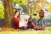 Young woman with bicycle sitting on a green grass and reading a newspaper in a park