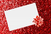 Christmas Sheet Of Paper With Bow On Red Defocused Background