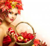Beauty Autumn Woman with Ripe Red Organic Apples. Beautiful Fashion Model Girl with Autumnal Hairstyle and Make up. Harvest Concept. Autumn Leaves. Fall