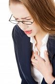 Beautiful business woman touching her chest, feeling unwell. Heart attach, health concept. Isolated on white.
