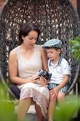 Mother and son holding retro camera