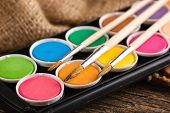 stock photo of bristle brush  - Oil paints and brushes to paint laid on the table in the composition - JPG
