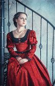 stock photo of stairway  - Beautiful young woman in red medieval dress on the stairway - JPG