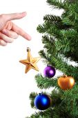 Hand Decorating Christmas Tree With Golden Star
