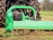 foto of grass-cutter  - tractor machine lawnmower cutting grass along ground field  - JPG
